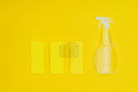 top view of rags and spray bottle isolated on yellow