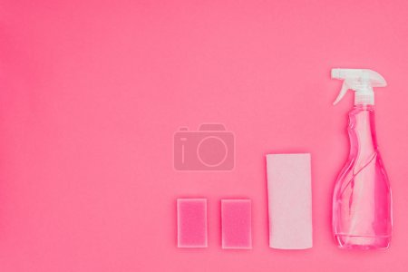 top view of pink washing sponges, rag and spray bottle isolated on pink