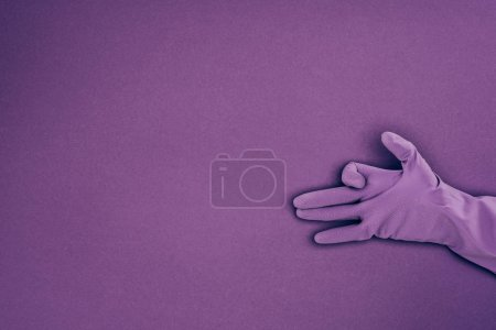 Photo for Cropped image of woman showing sign with hand in rubber protective glove isolated on violet - Royalty Free Image