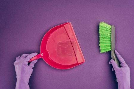 cropped image of woman holding scoop and brush isolated on violet