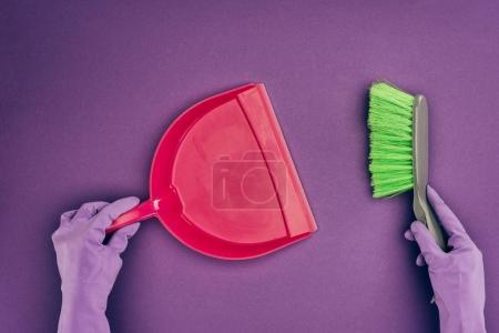 Foto de Imagen recortada de la mujer que sostiene la pala y cepillo aislados en violeta - Imagen libre de derechos