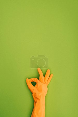 cropped image of woman showing ok sign in protective rubber glove isolated on green