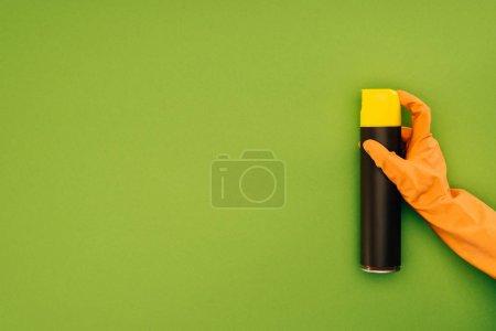 Foto de Imagen recortada de la mujer que sostiene la botella del aerosol aislado en verde - Imagen libre de derechos