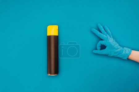 cropped image of woman showing ok sign near spray bottle isolated on blue