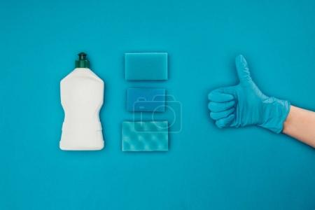 cropped image of woman showing thumb up in rubber protective glove isolated on blue