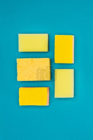top view of yellow washing sponges isolated on blue