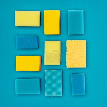 top view of yellow and blue washing sponges isolated on blue