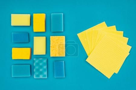 top view of yellow and blue washing sponges and rags isolated on blue