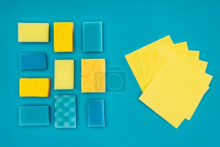 Photo for Top view of yellow and blue washing sponges and rags isolated on blue - Royalty Free Image