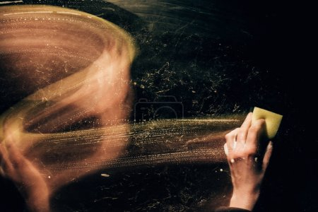 cropped image of woman cleaning surface with washing sponge