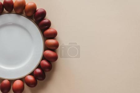 top view of chicken easter eggs around plate on beige with copy space