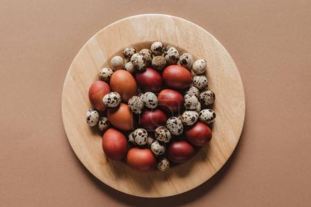 top view of chicken and quail easter eggs on wooden plate