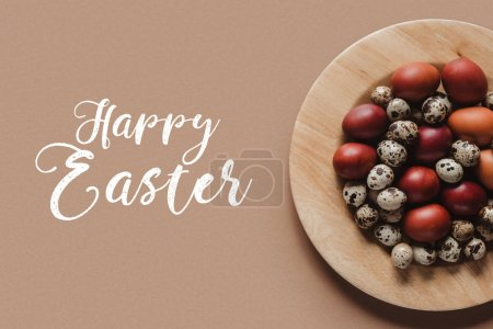 top view of chicken and quail easter eggs on wooden plate with Happy Easter lettering