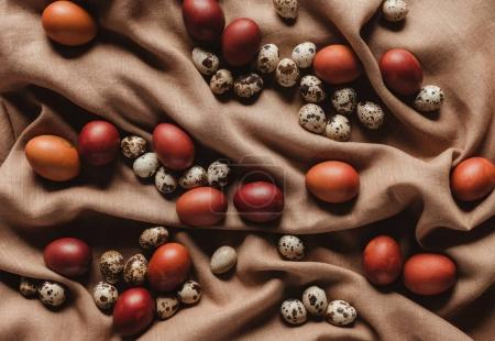 top view of easter painted eggs and quail eggs on linen tablecloth