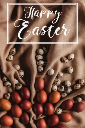 top view of easter painted eggs and quail eggs on linen tablecloth with Happy Easter inscription