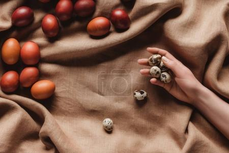 cropped view of hand with quail eggs on tablecloth with easter eggs