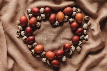 heart shaped easter eggs and quail eggs on linen tablecloth