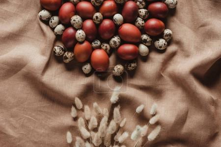 top view of easter painted eggs and quail eggs on linen tablecloth with ears