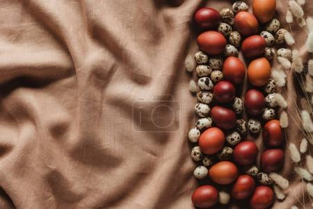 top view of chicken eggs and quail eggs on linen tablecloth with copy space