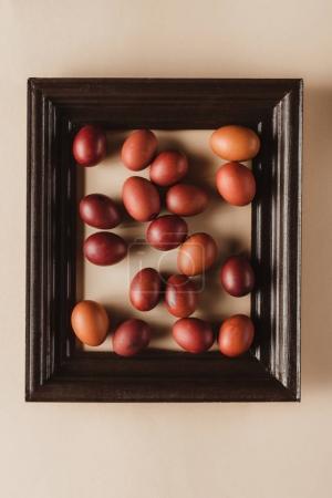 Photo pour Vue de dessus des œufs peints dans cadre en bois sur fond beige - image libre de droit