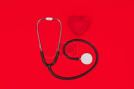 Photo pour Vue du dessus du stéthoscope et du coeur rouge isolés sur la table rouge, concept de journée mondiale de la santé - image libre de droit