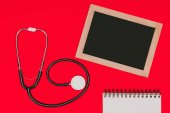 top view of blank chalkboard, notebook and stethoscope isolated on red tabletop, world health day concept