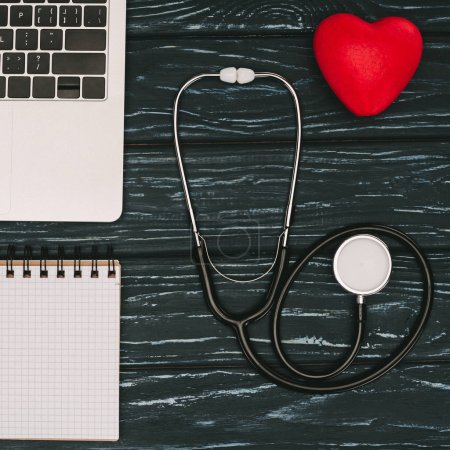 top view of arranged laptop, empty notebook, red heart and stethoscope on dark wooden tabletop