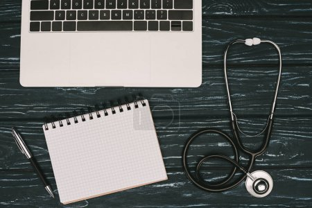 top view of arranged laptop, empty notebook, pen and stethoscope on dark wooden tabletop