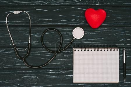 Photo for Flat lay with arranged red heart, stethoscope and empty notebook on dark wooden tabletop, world health day concept - Royalty Free Image