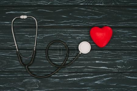 flat lay with red heart and stethoscope on dark wooden tabletop, world health day concept