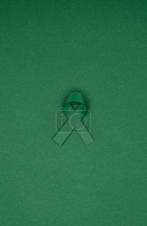 Photo pour Vue rapprochée du ruban vert de sensibilisation à la scoliose, symbole de santé mentale isolé sur la table verte - image libre de droit