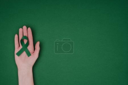 Photo pour Plan recadré de la main féminine avec ruban de sensibilisation vert pour Ruban de sensibilisation vert pour la scoliose, symbole de santé mentale isolé sur la surface verte - image libre de droit