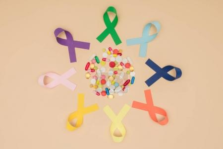 flat lay with arranged pills and colorful ribbons around isolated on beige tabletop, world health day concept