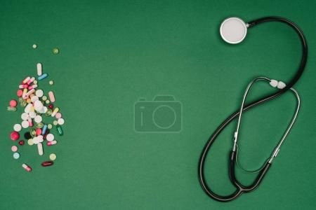 flat lay with arranged pills and stethoscope isolated on green tabletop, world health day concept