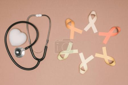 top view of arranged heart, stethoscope and colorful ribbons isolated on beige surface, world health day concept