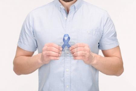 Photo pour Vue partielle de l'homme avec le ruban bleu de sensibilisation isolé sur blanc, notion de cancer du côlon - image libre de droit