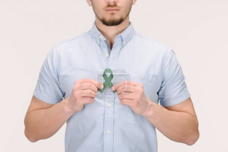 Photo for Partial view of man with green awareness ribbon for Adrenal Cancer, Aging research awareness, BiPolar Disorder isolated on white - Royalty Free Image