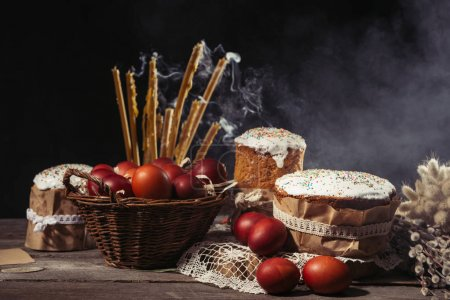 painted eggs in basket, candles with smoke and homemade easter cakes on wooden table