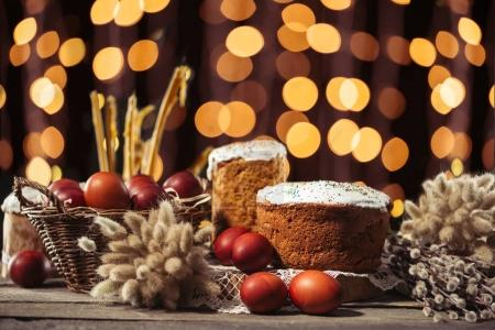 Photo for Easter cakes and painted chicken eggs, willow twigs and candles on wooden table with bokeh background - Royalty Free Image