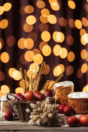 Photo pour Chatons, bougies, gâteaux de Pâques et œufs de poulet peints sur une table en bois avec fond bokeh - image libre de droit