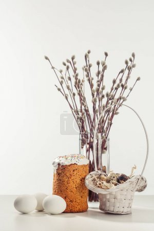 quail eggs in basket, chicken eggs, easter cake and willow twigs in vase on grey