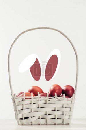 painted easter eggs in basket and funny rabbit ears on grey