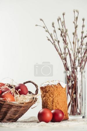 Photo pour Brindilles de saule dans un vase, gâteau de Pâques et oeufs de poulet peints dans le panier sur gris - image libre de droit