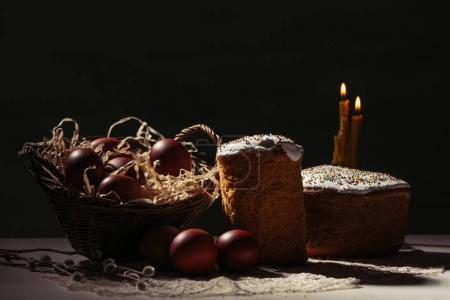 basket with painted chicken eggs, easter cakes and burning candles on black