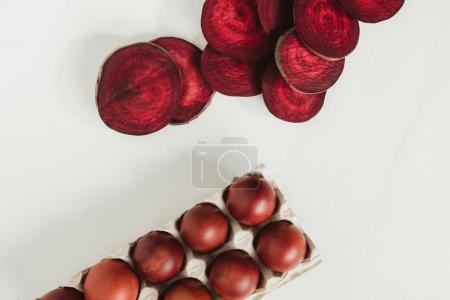 top view of painted chicken eggs in egg box and beetroot slices on grey