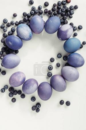 circle made from violet painted easter eggs and blueberries on grey