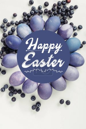 purple painted chicken eggs, blueberries and happy easter inscription on grey