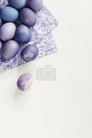 top view of purple painted easter eggs with napkin on grey