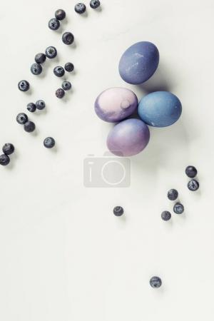 top view of traditional painted violet easter eggs and blueberries on grey
