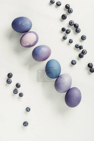 top view of blueberries and painted purple easter eggs on grey